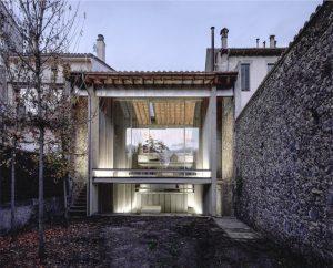 Ampliación de vivienda de piedra con vidrio y metal