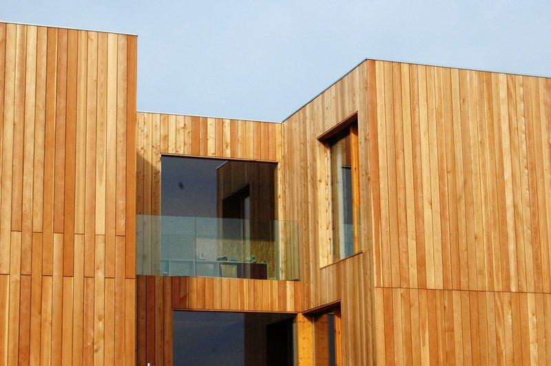 Vviienda con revestimiento de madera vertical y barandilla de vidrio