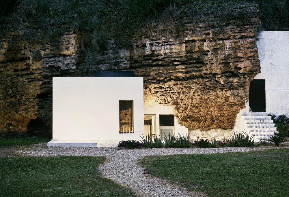 Exterior de caja blanca integrada en la piedra