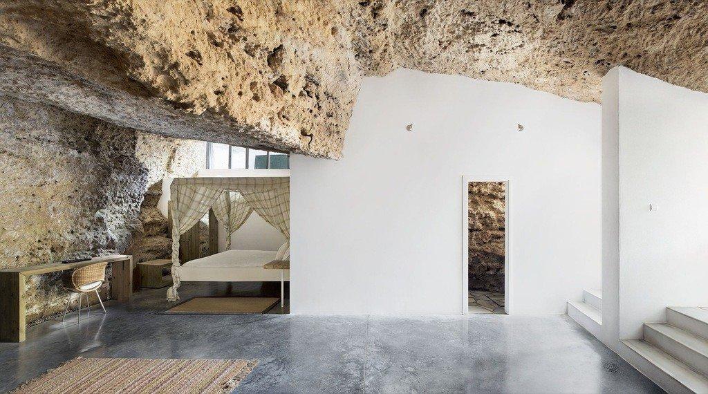 Imagen interior con muros blancos y roca