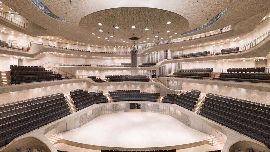 Interior de sala de conciertos de madera clara y formas geométricas