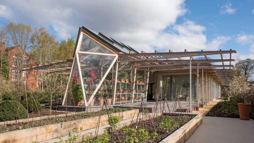 Edificio tipo invernadero de cristal y con mucha vegetación
